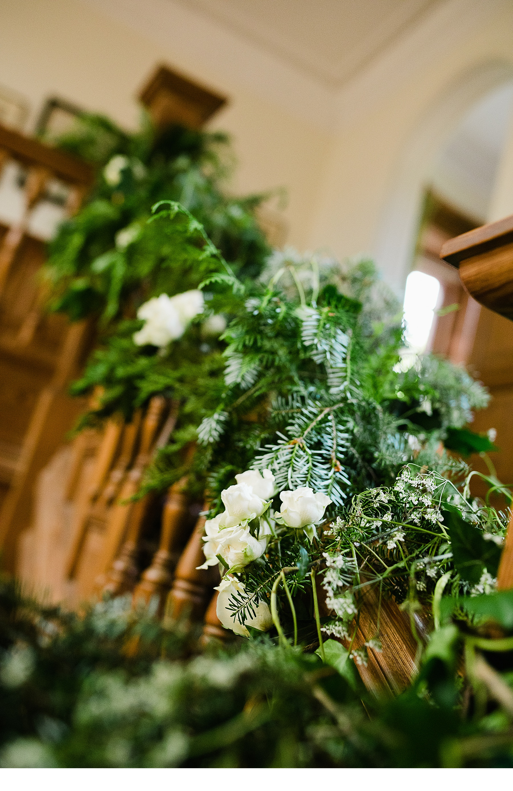 Green and white floral stairway decoration with roses and pine