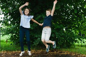 Brother and sister jumping in the air in a park